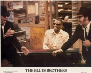 A USA lobby card featuring a scene from The Blues Brothers (1980). The scene includes Dan Ackroyd, Ray Charles and John Belushi